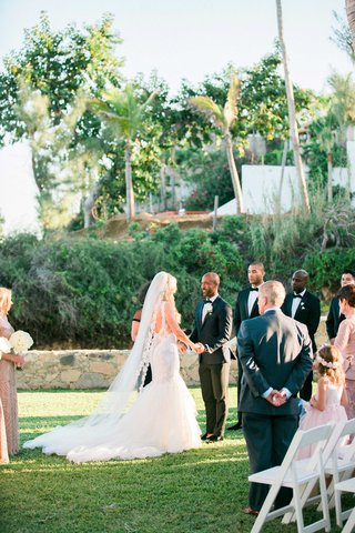 a-bride-and-groom-say-their-vows-in-front-of-family-and-friends-on-green-lawn-near-palm-trees