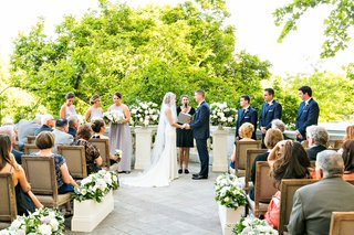 wedding-guests-in-wood-chairs-flower-boxes-stone-aisle-bride-and-groom-woman-officiant-bridesmaids