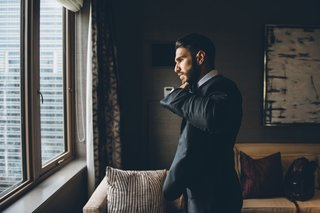 groom-in-suit-preparing-for-wedding-ceremony-in-grooms-suite-chicago