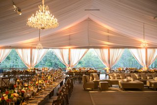 tent-wedding-in-texas-with-chandeliers-lighting-long-rustic-wood-tables-and-low-centerpieces