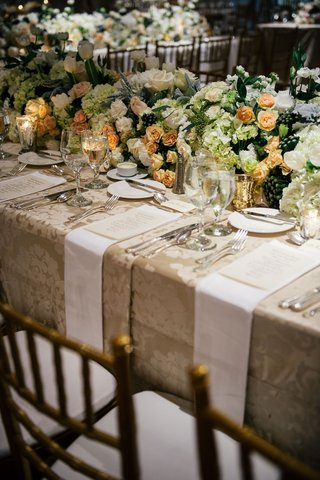wedding-reception-tablescape-low-flower-runner-with-beige-damask-linen-gold-candle-votives-napkins