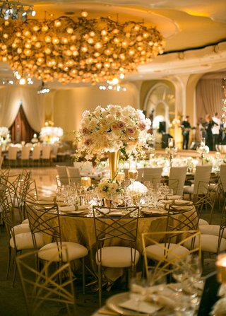 gold-lighting-gold-centerpiece-blush-ivory-flower-centerpiece-gold-chairs-birch-candles