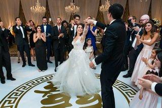 bride-in-monique-lhuillier-wedding-dress-groom-in-tuxedo-dancing-on-custom-dance-floor-gold-emblem