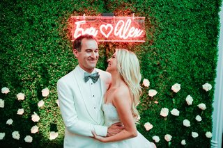 groom-in-white-tuxedo-hugging-bride-in-strapless-dress-underneath-neon-sign-with-names-on-boxwood
