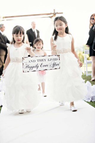 flower-girls-carrying-sign-up-the-aisle-end-of-ceremony-cute-fairy-tale-saying-outdoor-california
