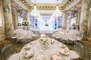 clear-back-chairs-white-and-gold-reception-decor-marble-columns-white-flower-centerpieces