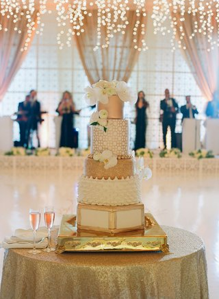 wedding-cake-white-and-gold-different-tiers-white-flowers-champagne-gold-cake-table
