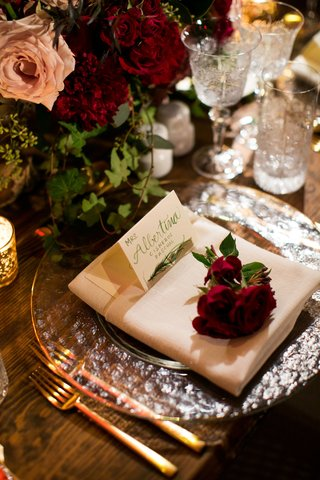 green-calligraphy-on-place-card-at-head-table-clear-charger-plate-gold-rim-flatware-greenery-and-red