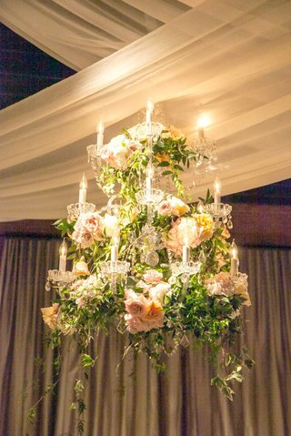 a-hanging-chandelier-bedecked-with-greenery-and-white-blush-and-orange-flowers