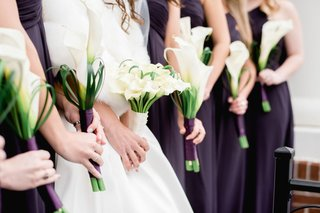 bride-and-bridesmaids-carrying-white-calla-lily-bouquet-nosegay-flowers-wrapped-with-white-purple