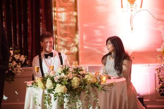 bride-in-elan-groom-in-armani-without-jacket-suspenders-newlyweds-talk-at-sweetheart-table