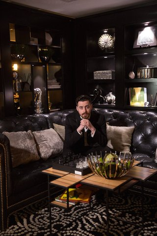 groom-in-tuxedo-on-tufted-black-couch-at-renaissance-hotel-in-cincinnati