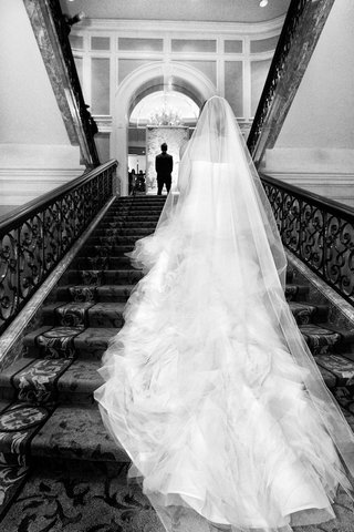 black-and-white-photo-of-bride-in-vera-wang-walking-up-stairs-to-groom-in-hugo-boss