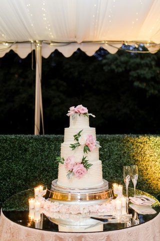four-tier-wedding-cake-with-pink-flowers-and-greenery-on-mirror-table