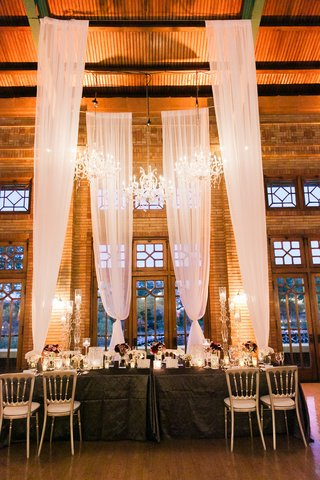 wedding-reception-table-with-tall-drapery-canopy-chandeliers-purple-flowers-low-centerpieces