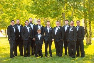 groom-in-pink-bow-tie-with-groomsmen-and-ring-bearer-in-blue-grey-bow-ties