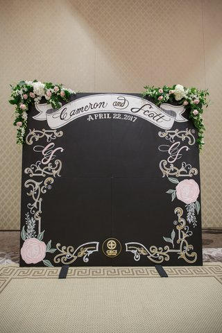 chalk-board-photo-booth-backdrop-at-wedding-with-flowers-on-top