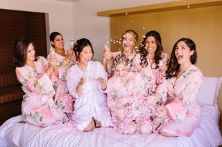 pink-confetti-poppers-pink-bridesmaids-robes-with-bride-on-bed-getting-ready-shot