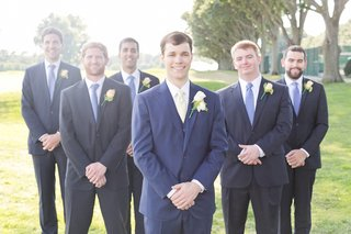 groom-in-royal-blue-suit-and-yellow-tie-groomsmen-in-navy-blue-suits-and-light-blue-ties