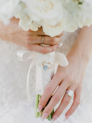 white-bouquet-with-white-wrap-blue-stone-ring-attached-ribbon-large-engagement-ring-manicure-french