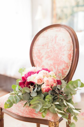 wedding-bouquet-on-top-of-upholstered-vintage-antique-wood-chair-greenery-with-pink-and-white-flower