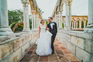 bride-and-groom-walking-down-column-path-at-the-ocean-club-four-seasons-bahamas