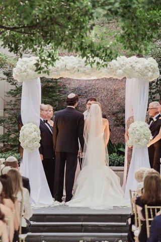 bride-in-low-back-mermaid-wedding-dress-and-groom-in-suit-and-yarmulke-under-chuppah-white-drapery