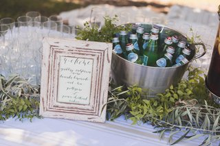 wedding-ceremony-outdoors-rustic-frame-calligraphy-sign-with-lemonade-bucket-of-pellegrino-and-wine