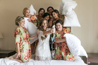 bridesmaids-in-green-floral-robes-prepare-to-hit-the-bride-with-pillows-as-she-pops-champagne