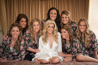 bride-in-white-robe-with-bridesmaids-in-dark-robes-with-pink-floral-pattern-dottie-palmer