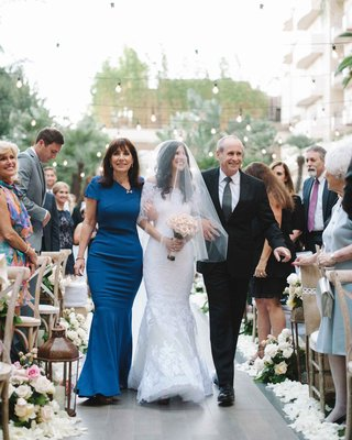 bride-in-marchesa-mermaid-wedding-dress-walks-down-aisle-with-blue-mother-of-the-bride-dress