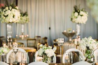 wedding-reception-white-drapery-white-rim-round-back-chairs-gold-linens-white-hydrangea-centerpieces