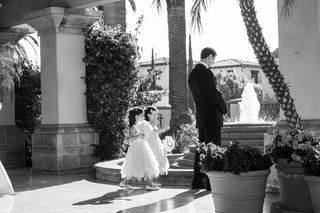 black-and-white-photo-of-two-maid-of-honor-twin-daughters-walking-up-to-groom-for-first-look