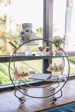 wedding-reception-with-an-art-deco-dessert-cart-carrying-a-blue-wedding-cake-macarons-mini-cakes