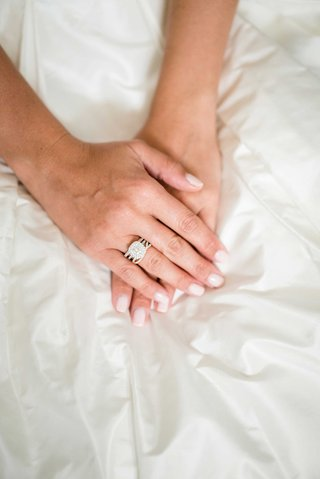 double-halo-engagement-ring-on-brides-hand-with-light-manicure-nails