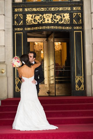 woman-in-wedding-dress-kissing-man-in-front-of-the-plaza-hotel