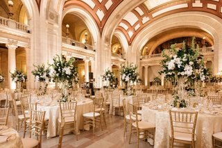 wedding-reception-marble-hall-arches-columns-high-ceilings-gold-chairs-tall-centerpiece-greenery
