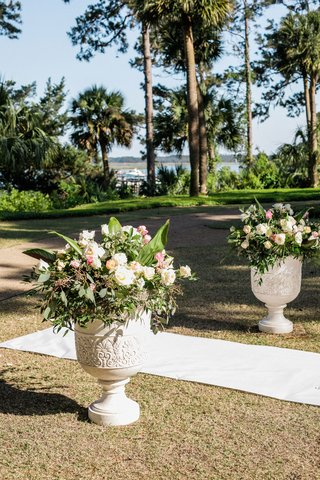 wedding-ceremony-outdoor-urn-with-greenery-white-pink-flowers-trees-overlooking-water-grass