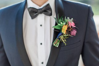 groom-in-navy-tux-with-black-lapel-leather-bow-tie-and-boutonniere-with-colorful-flowers