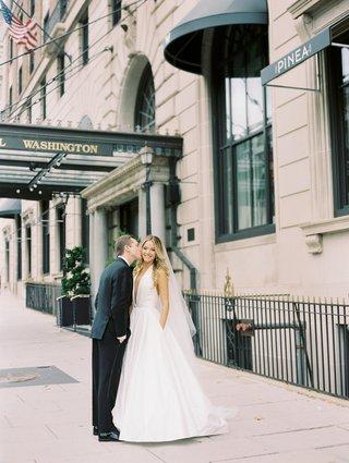 groom-kissing-brides-cheek-wedding-dress-with-pockets-romona-keveza-wedding-dress-deep-v