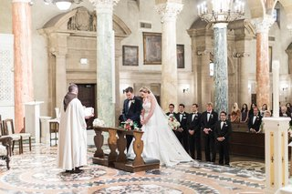 bride-and-groom-at-altar-wedding-ceremony-marble-columns-st-andrews-catholic-church-traditional
