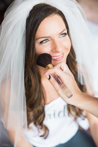 bride-wearing-veil-gets-makeup-applied