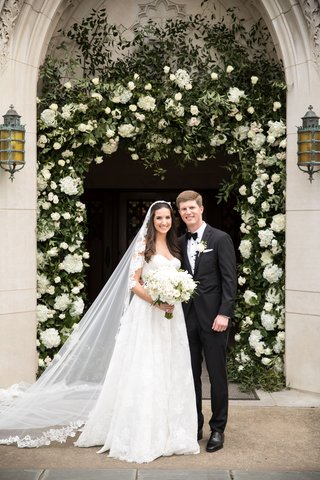 bride-in-lace-trim-wedding-veil-with-groom-in-suit-bow-tie-in-front-of-church-arch-greenery-white