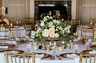 gold-chairs-around-white-table-with-gold-fotted-vase-with-roses-and-white-flowers-greenery-candles