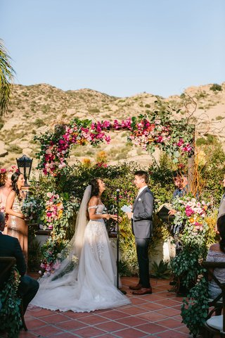 wedding-ceremony-mountain-view-light-pink-pink-yellow-orange-flowers-sunny-vow-exchange-ranch-venue