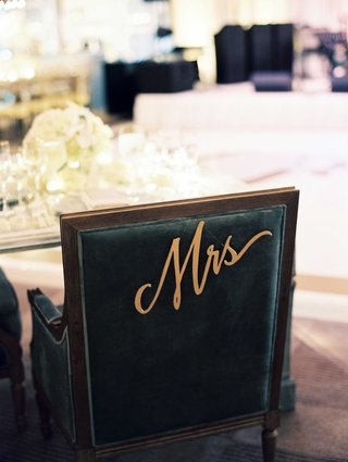 black-chair-at-sweetheart-table-with-mrs-sign-dangling-from-back-in-modern-cursive-calligraphy