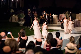 wedding-ceremony-night-outdoor-stage-aisle-flower-girls-in-pink-dresses-holding-hands