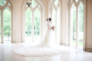 bride-in-chateau-wedding-venue-tall-windows-wedding-dress-cathedral-train-and-veil