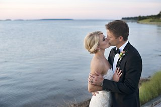 bride-in-a-lace-anne-barge-gown-kisses-groom-in-black-tuxedo