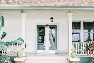 wedding-dress-lace-illusion-neckline-hanging-up-on-door-frame-porch-tropical-print-bench-palm-leaves